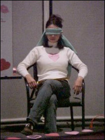 "Christine sits blindfolded as the contestants are led onto the Festival stage. In Singled Out, the ""date"" is not supposed to see the contestants who have not been eliminated, so any time a contestant and the ""date"" were to be in potential eye contact, Christine got blindfolded."
