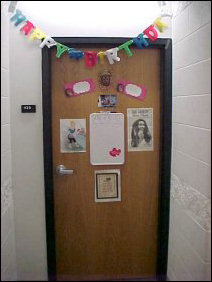 "This door contains signs and a festive ""Happy Birthday"" banner across it. You can see a close-up of the sign on the left part of the door below."