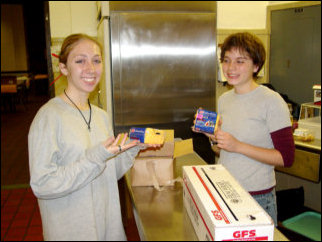 """Mary and Maggie strike a """"cheesy"""" pose while helping prepare the food for lunch."""