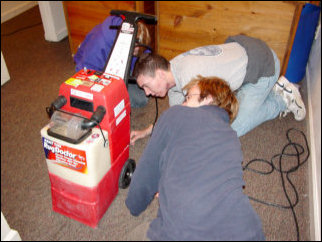 One of the Rug Doctor machines broke down on us! Here, Nicole, Mark, and Spencer take a look at it to try and figure out what was wrong with it. Turned out that it was nothing we could fix on the spot, but thankfully we had a backup, as Kathleen had her own Bissell steam cleaner. We used that.